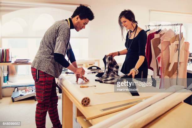 Female fashion designer working with pattern maker on new creations.