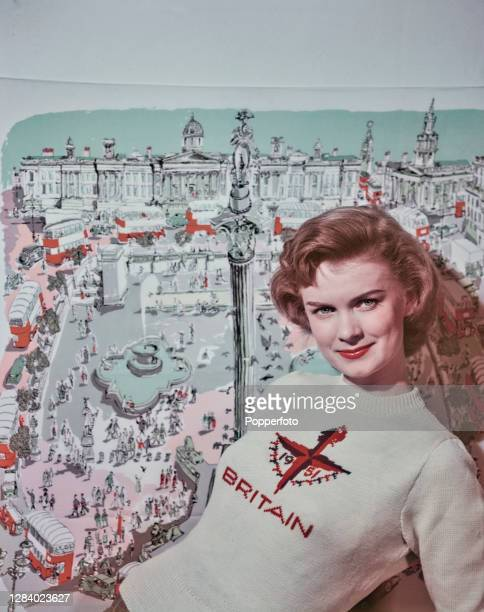 Female fashion model Marianne Burwood, wearing a jumper with the Festival of Britain emblem, poses in front of a scarf featuring a Trafalgar Square...