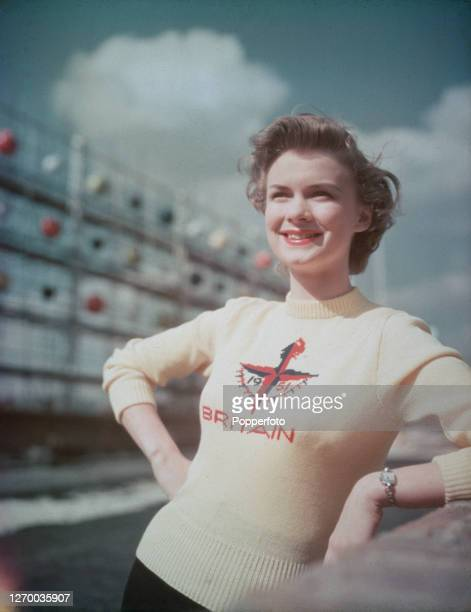 Female fashion model Marianne Burwood wears a jumper with the Festival of Britain emblem as she poses on a balcony overlooking the festival...