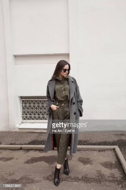 female fashion model, posing for a full length photo, wearing green suit, urban fashion photography - autumn winter fashion collection stockfoto's en -beelden