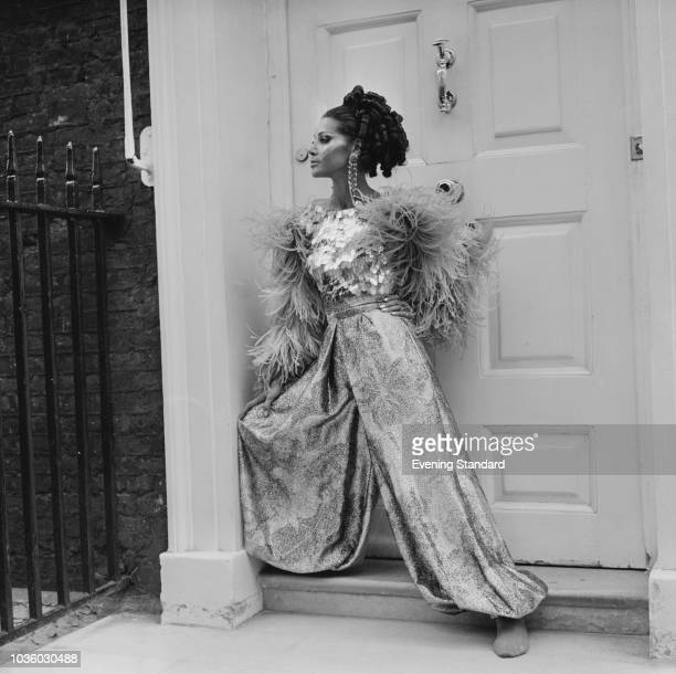 A female fashion model styling a feather jacket sequin top and wide leg printed trousers UK 16th July 1968