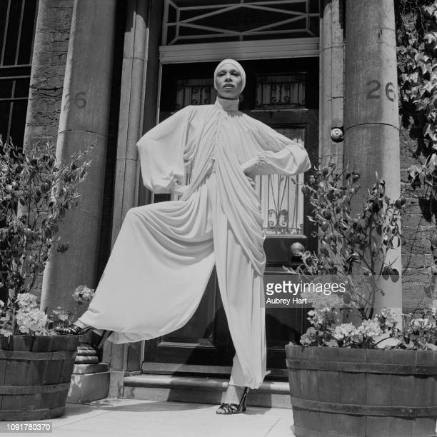 A female fashion model wearing a drapped high collar neck top with matching extra wide leg trousers and hat UK 3rd June 1975