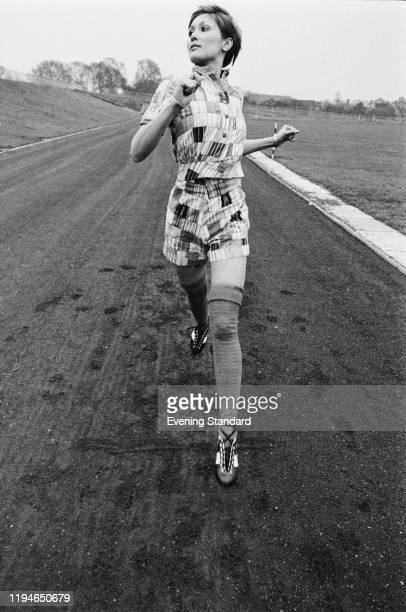 Female fashion model wearing a quilted short sleeved jacket and matching shorts with over the knee socks, runs along a cinder running track, 22nd...