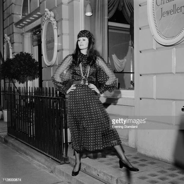 Female fashion model wearing Christian Dior outfit: a printed dress with transparent sleeves, matching headscarf, and long pendants, UK, 4th March...