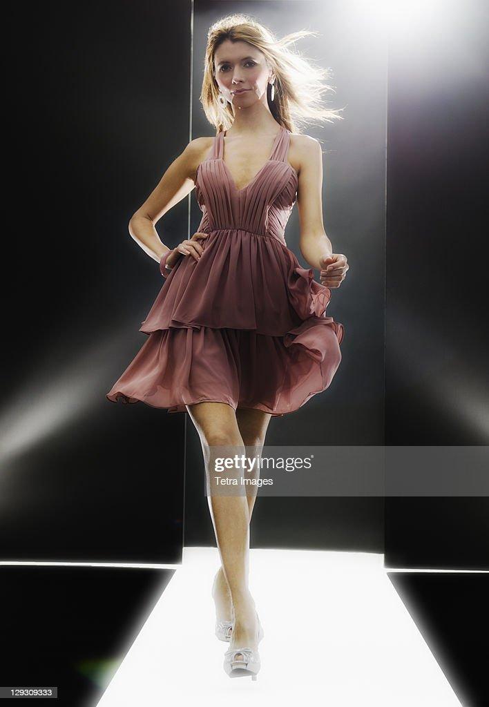 Female fashion model wearing dress on catwalk : Foto de stock