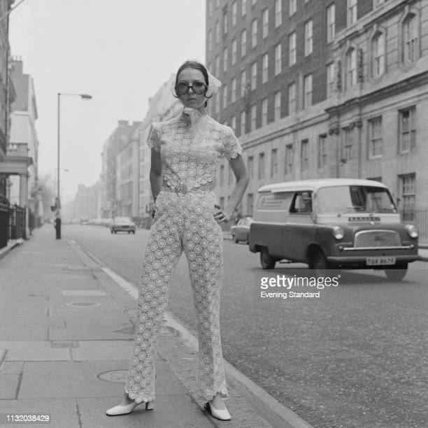 A female fashion model wearing embroidered cropped on side lace jumpsuit with matching veil and sunglasses London UK 3rd April 1969