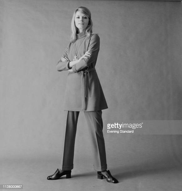 A female fashion model wearing high neck tunic with belt matching suit trousers and loafers shoes UK 9th October 1968