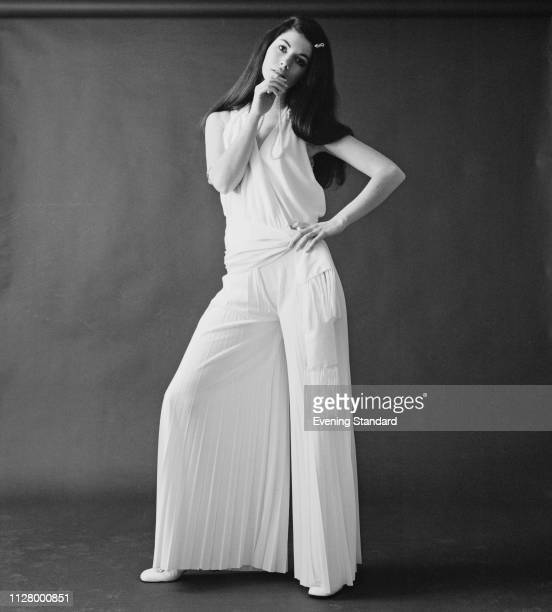 A female fashion model wearing jersey pleated wide leg trousers and white west UK 10th February 1969