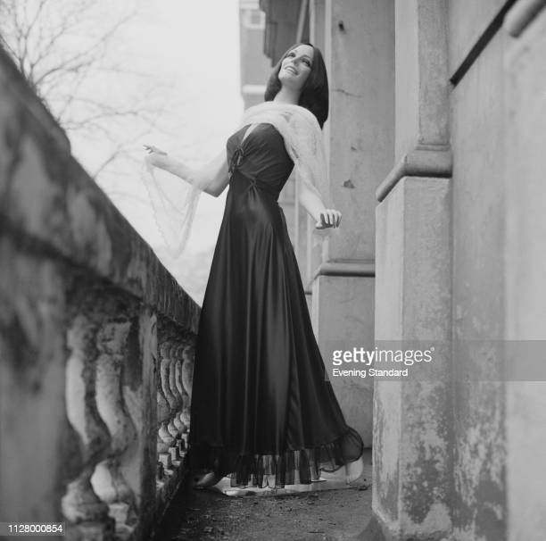 Female fashion model wearing long evening gown and embroidered white shawl, UK, 27th February 1969.