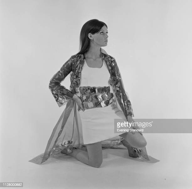 Female fashion model wearing white crepe dress and vinyl transparent coat, UK, 30th September 1968.