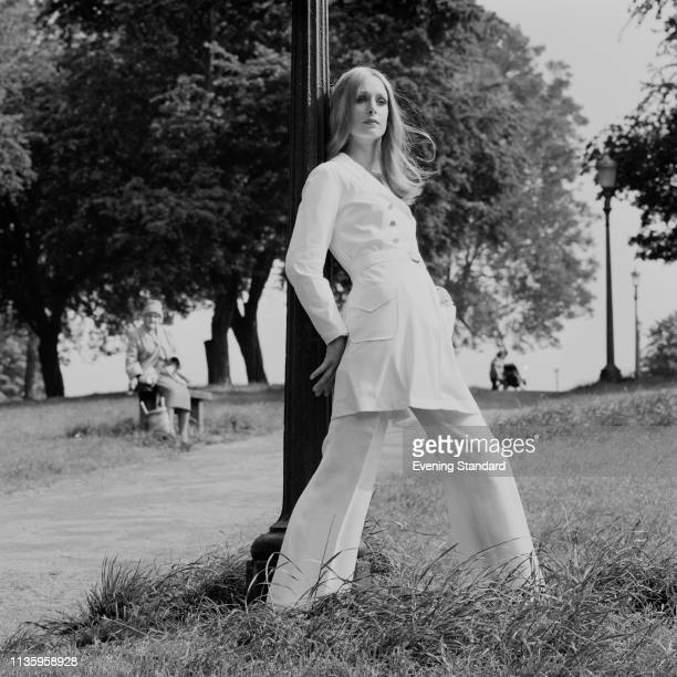 Female fashion model wearing white raincoat and flared white trousers during a photo shoot at Primrose Hill, London, UK, 16th June 1969.