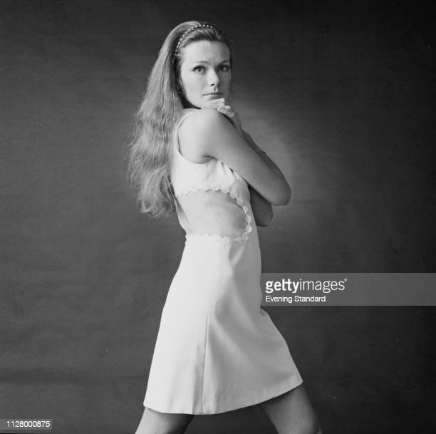 Female fashion model wearing white sleeveless dress during a photo shoot, UK, 11th March 1969.