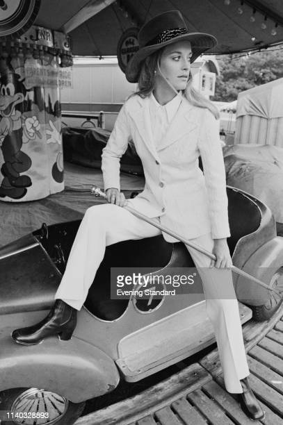 A female fashion model wearing white trouser suit and hat near a Carousel UK 10th September 1969