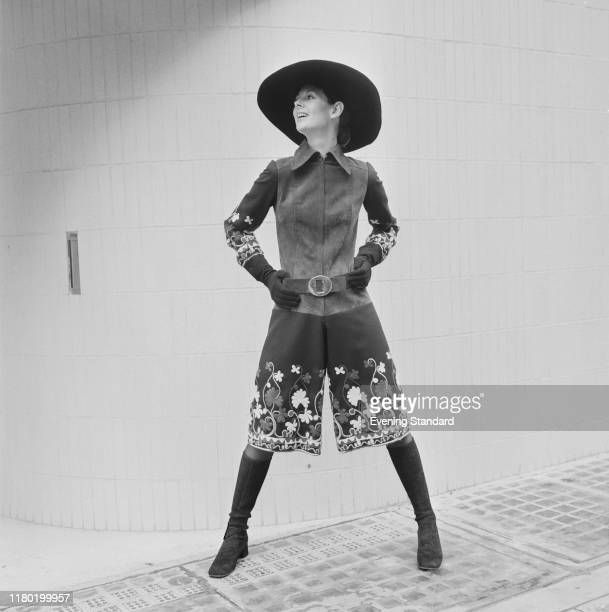 A female fashion model wears a culotte dress in suede and fabric with suede boots and wide brimmed hat on a street in London on 8th September 1970