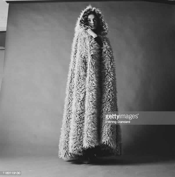 Female fashion model wears a fake Mongolian lamb fur cloak in a studio in London on 16th November 1970.