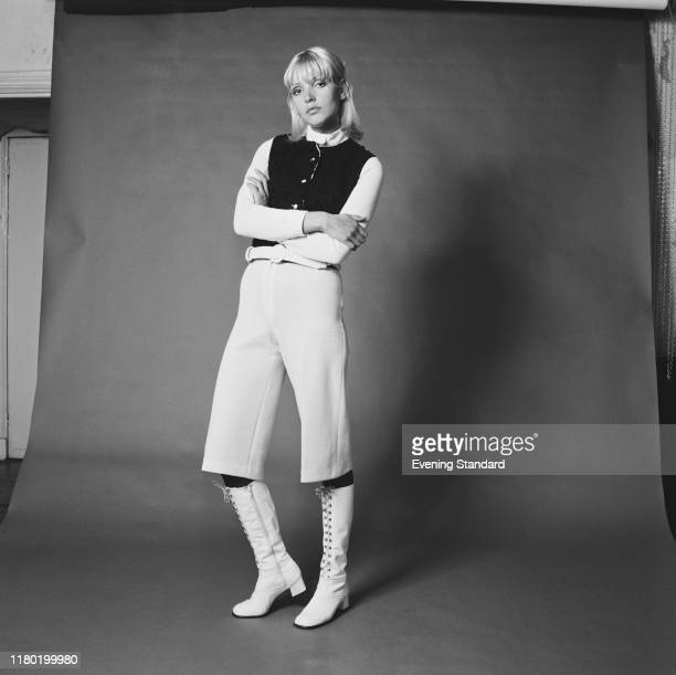 Female fashion model wears a pair of cropped knee length white trousers and matching lace up boots during a studio shoot in London on 28th September...