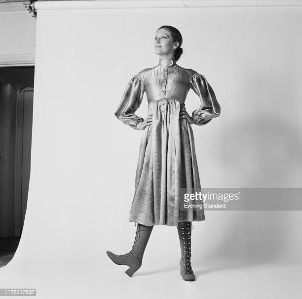 A female fashion model wears a Russian look evening dress with lace up boots at a fashion shoot in a studio 31st July 1970