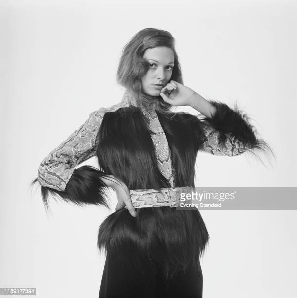 Female fashion model wears a wild monkey fur and snakeskin jacket with matching belt, UK, 7th December 1970.