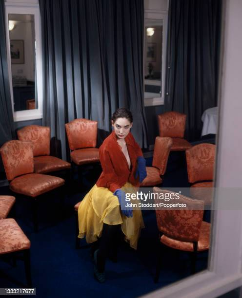 Female fashion model wears an outfit by Jasper Conran, comprising a copper coloured short jacket with scalloped edges, a yellow chiffon wrap skirt...