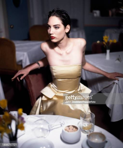 Female fashion model wears an outfit by Jasper Conran, comprising a gold satin strapless dress with pocket flaps at the hip and a knee length skirt,...