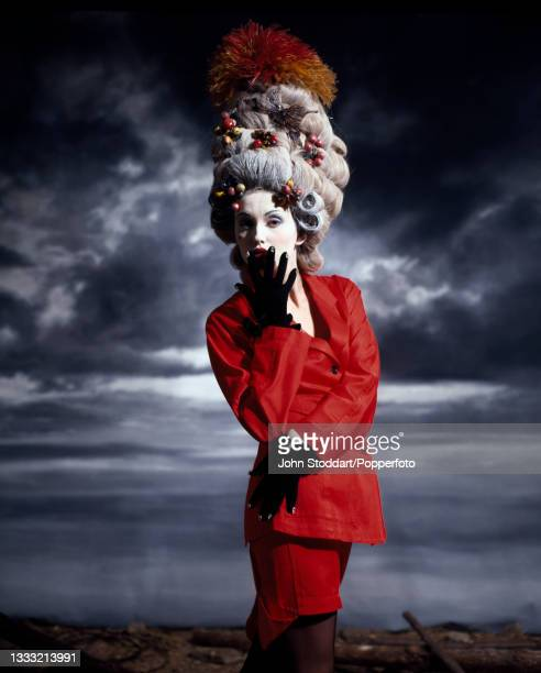Female fashion model wears an outfit by John Galliano, comprising a red two piece suit with an asymetric hem on the skirt and black gloves, she wears...