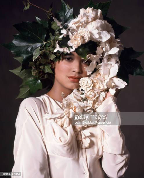 Female fashion model wears an outfit by John Galliano, comprising a button front dress in cream silk with curved draped sleeves and angular pleating...