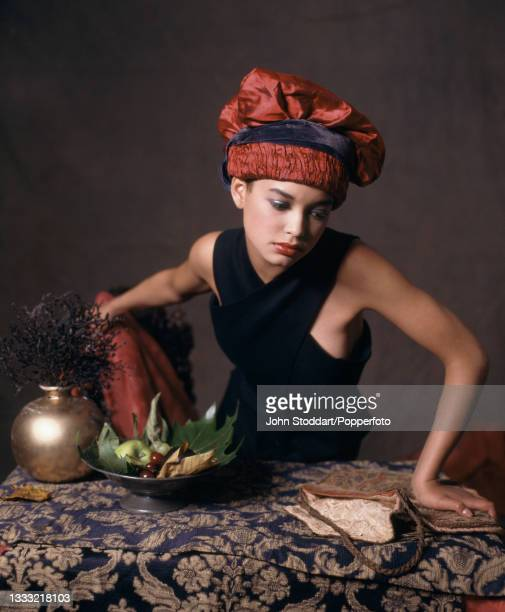 Female fashion model wears an outfit by John Galliano, comprising a navy blue sleeveless dress with crossover front and a rust coloured turban style...