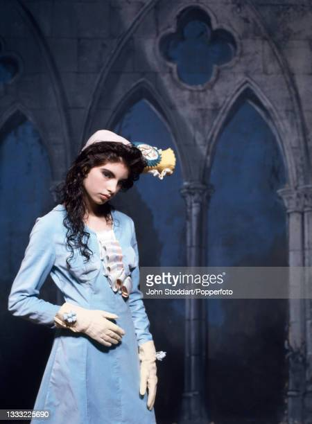 Female fashion model wears an outfit by John Galliano, comprising a light blue satin dress with A-line skirt and a concertinaed ruffle down the front...