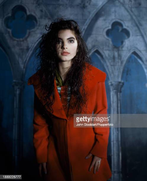 Female fashion model wears an outfit by John Galliano, comprising a red felt coat with oversized collar, a red and blue concertinaed neck ruffle is...