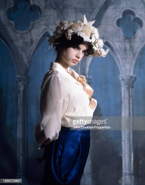 Female fashion model wears an outfit by John Galliano, comprising an electric blue structured skirt and a cream crepe de chine blouse with ruffles...