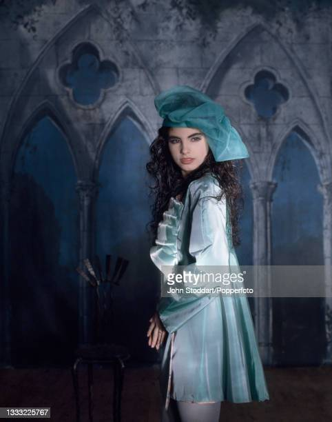 Female fashion model wears an outfit by John Galliano, comprising an aqua blue satin coat dress in a short, swing style with a concertinaed ruffle...