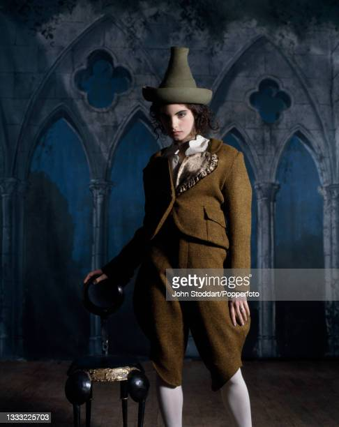 Female fashion model wears an outfit comprising pieces by John Galliano and Vivienne Westwood, including a Vivienne Westwood cropped jacket in brown...