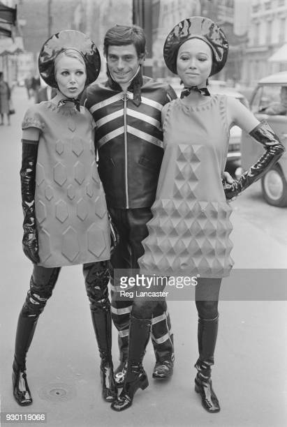 Female fashion models wearing 'Cardin' fabric threedimensional dresses with raised geometrical patterns and male model wearing black leather overall...