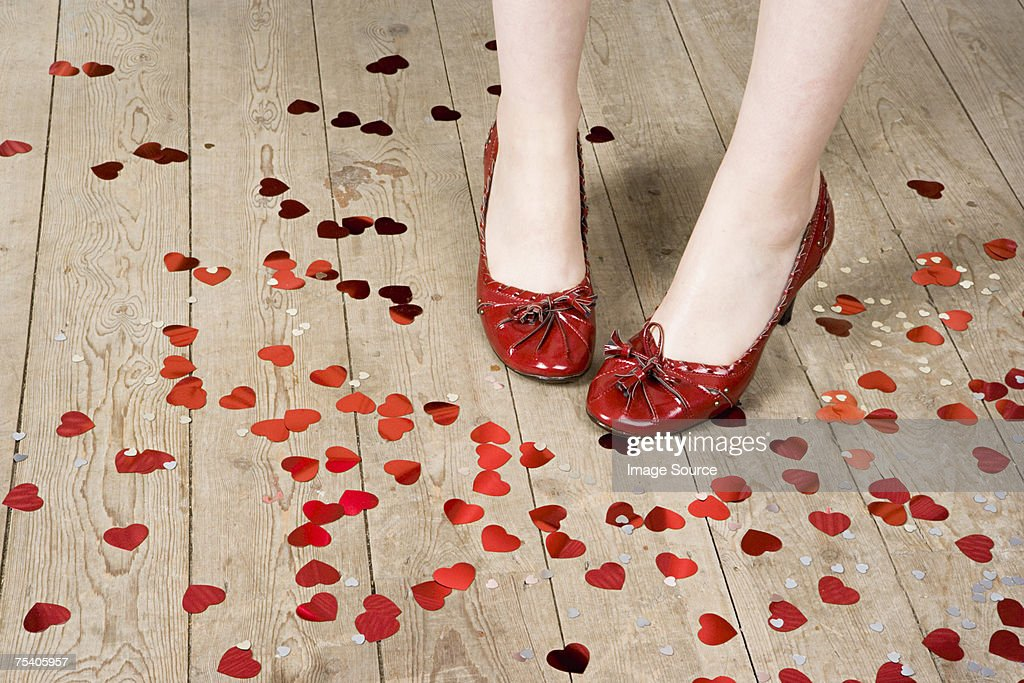 Female feet and heart shaped confetti : Stock Photo
