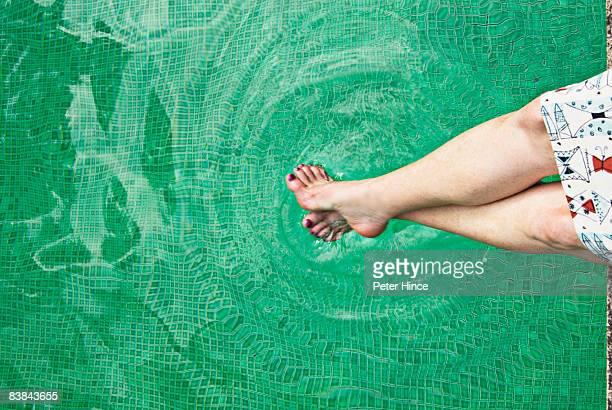 female feet dipping into green mosaic pool - 人のつま先 ストックフォトと画像
