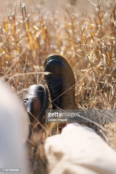 female feet in black leather boots on grass - bottes marron photos et images de collection
