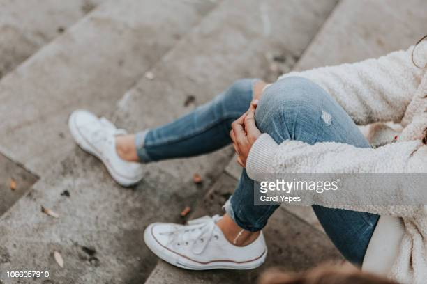 female feet in jeans and sports shoes - jeans stock pictures, royalty-free photos & images