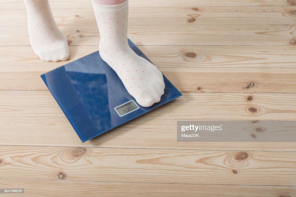 female feet in socks on the floor scales : Stock Photo