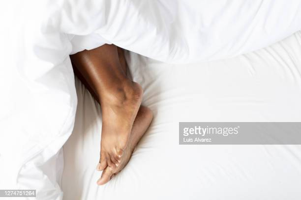 female feet under blanket - human foot stock pictures, royalty-free photos & images