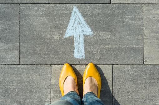 Female feet with arrow painted on the asphalt. 959324294
