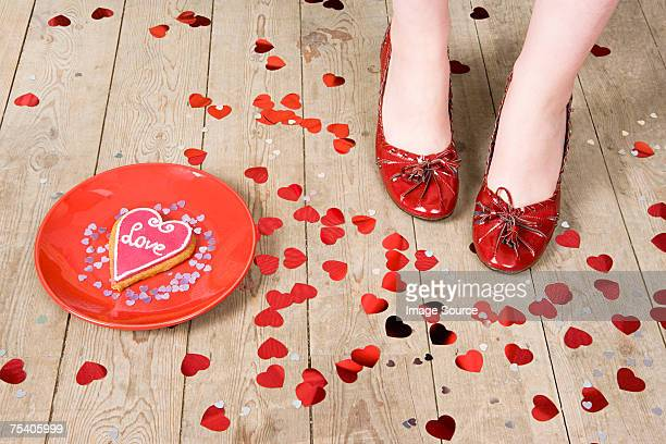Female feet with heart shaped confetti and biscuit