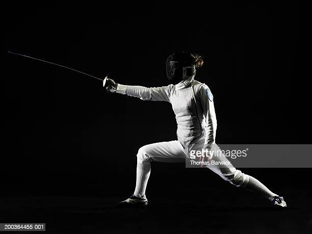 Female (14-16) fencer in defensive pose, side view