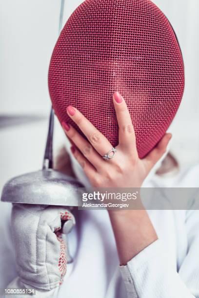 esgrimista feminina posando, mantendo a máscara de proteção - esgrima esporte de combate - fotografias e filmes do acervo