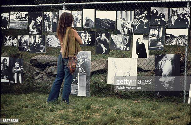 A female festival goer looks at a gallery of photographs hanging upon a chain link fence and exhibited at the Woodstock Music Festival Bethel NY...