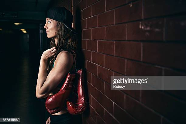 Female figher standing by a brick wall