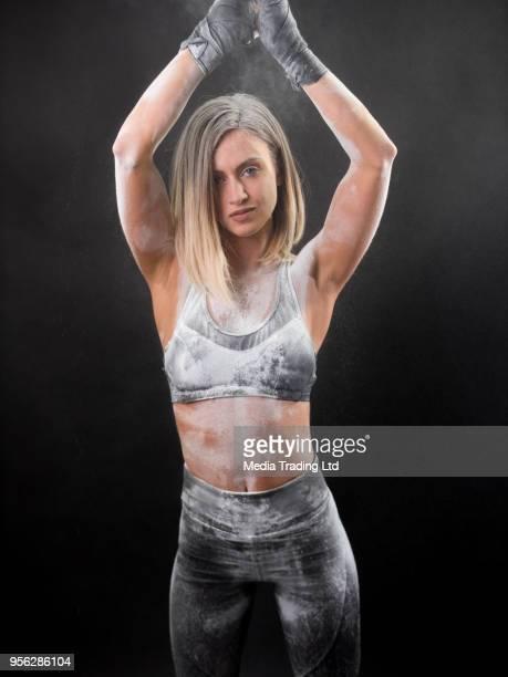 Combattant femelle couvert de poudre de talc blanche, regardant la caméra