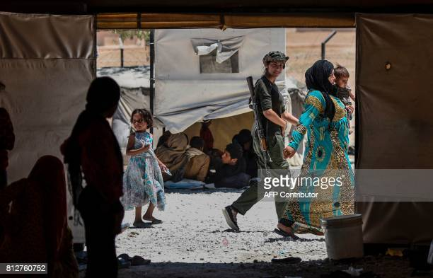 TOPSHOT A female fighter from the Kurdish Women's Protection Units walks between displaced Syrians who fled the countryside surrounding the Islamic...