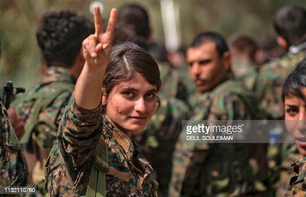 Female fighter of the US-backed Kurdish-led Syrian Democratic Forces flashes the victory gesture while celebrating near the Omar oil field in the...