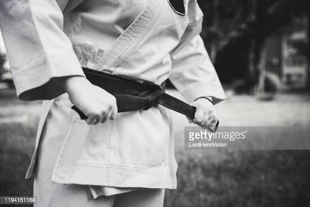 female fighter tightening karate belt - judo stock pictures, royalty-free photos & images