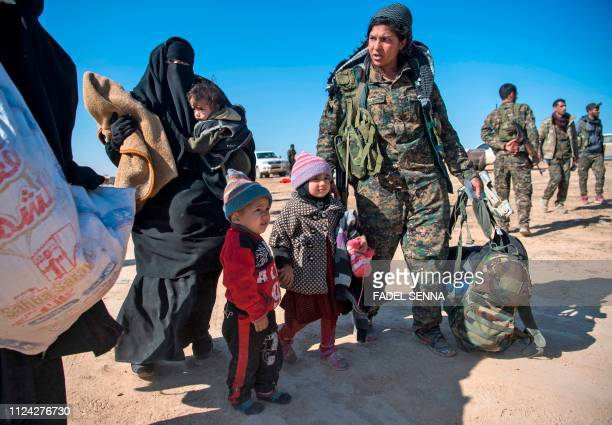 A female fighter with the USbacked Syrian Democratic Forces helps civilians fleeing from the Baghouz area in the eastern Syrian province of Deir...